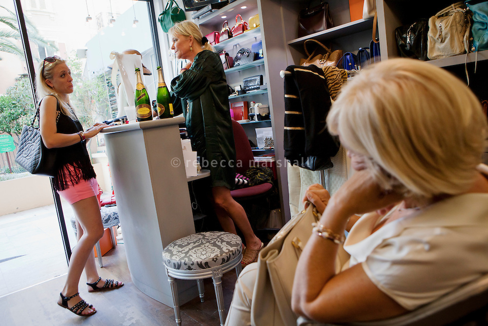 "Helen Rimsberg, Swedish owner of boutique 'Le Dressing', chats with her customers, Le Dressing, Rue Princesse Florestine, La Condamine, Monaco, 5 July 2013. The shop has many regular customers and Helen often opens a couple of bottles of champagne at the end of the day to share with her customers. ""We have a fridge full of champagne in the cupboard"" she says."