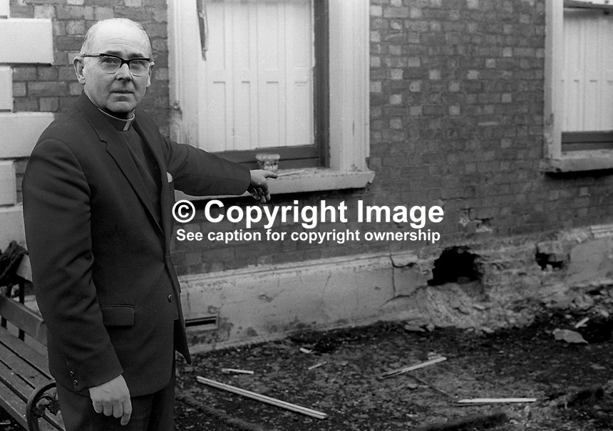 Rev Eamonn McEnaney, parish priest, Antrim, N Ireland, points to the damage where a loyalist bomb was placed outside the Parochial House. He was at home at the time but was uninjured. 5th April 1973. 197304050182a<br /> <br /> Copyright Image from Victor Patterson, 54 Dorchester Park, Belfast, UK, BT9 6RJ<br /> <br /> t1: +44 28 9066 1296 (from Rep of Ireland 048 9066 1296)<br /> t2: +44 28 9002 2446 (from Rep of Ireland 048 9002 2446)<br /> m: +44 7802 353836<br /> <br /> e1: victorpatterson@me.com<br /> e2: victorpatterson@gmail.com<br /> <br /> The use of my copyright images is subject to my Terms &amp; Conditions.<br /> <br /> It is IMPORTANT that you familiarise yourself with them. They are available on my website at www.victorpatterson.com.<br /> <br /> None of my copyright images may be used on a website unless they are visibly watermarked, i.e. &copy; Victor Patterson within the body of the visible image. Metadata denoting my copyright must NOT be deleted. <br /> <br /> Web use is extra at currently recommended NUJ rates.