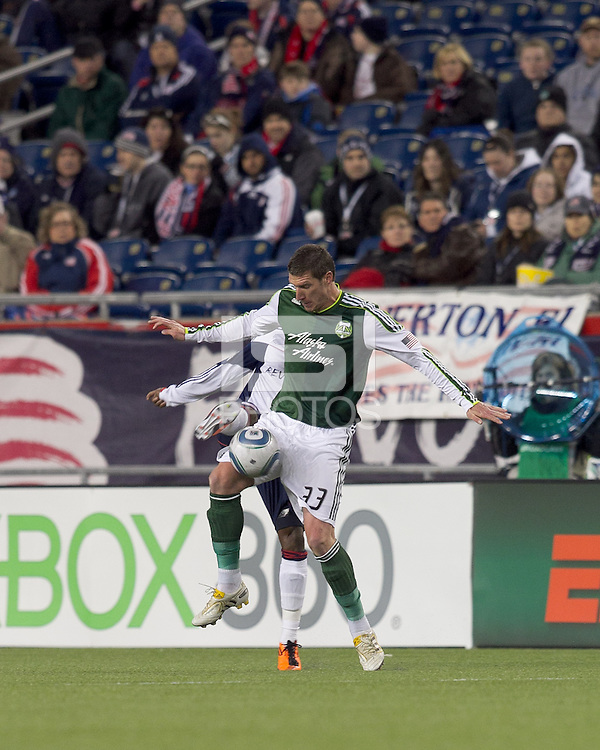 Portland Timbers forward Kenny Cooper (33) under pressure, attempts to control the ball. In a Major League Soccer (MLS) match, the New England Revolution tied the Portland Timbers, 1-1, at Gillette Stadium on April 2, 2011.