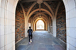 student walking thru duke archway on west campus