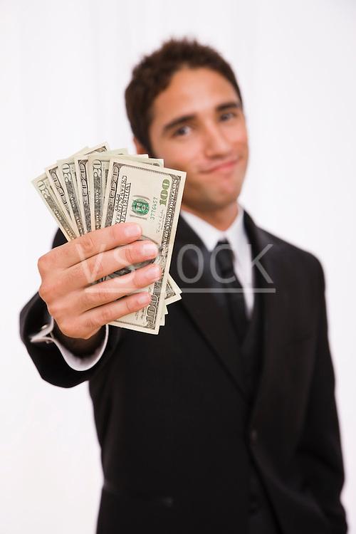 USA, Illinois, Metamora, Studio shot businessman holding fanned out banknotes
