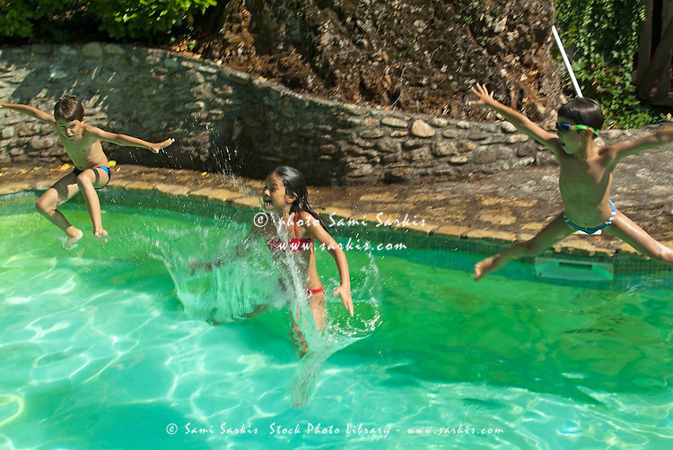 Young girl and two boys leaping into a swimming pool, Provence, France.