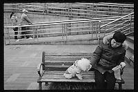 A local resident feeds her pet dog along the ancient Beijing-Hangzhou Grand Canal in Hangzhou, Zhejiang province, China, March 2013.