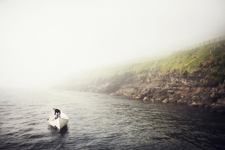 A man heads out into the fog in his small fishing boat in the Faroe Islands.