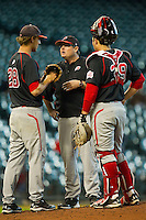 Utah Utes coach Mike Crawford #21 has a meeting on the mound with pitcher Zach Adams #28 and catcher Jo Jo Sharrar #39 during the game against the Baylor Bears at Minute Maid Park on March 5, 2011 in Houston, Texas.  Photo by Brian Westerholt / Four Seam Images