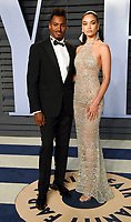 DJ Ruckus, left, and Shanina Shaik arrive at the Vanity Fair Oscar Party on Sunday, March 4, 2018, in Beverly Hills, Calif. (Photo by Evan Agostini/Invision/AP)