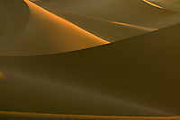 Sunrise on the sand dunes in Death Valley National Park. The sun rises over the Funeral Mountains, at  casting shadows across the dunes,  The temperature, in the mid 70's at sunrise, reaches 120 degrees later in the day. The wind continually changes the shape of the dunes but not their location.