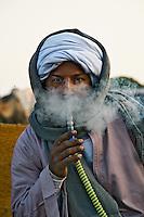 Egyptian camel trader smoking hookah pipe, camel market, Cairo, Egypt