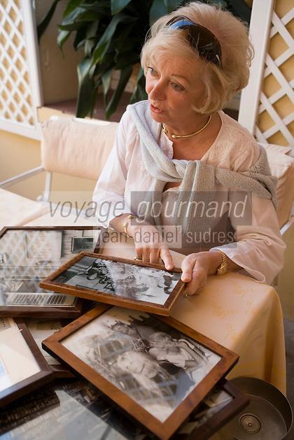 """Europe/Provence-Alpes-Côte d'Azur/83/Var/Saint-Tropez: Simone Durckstein  propriétaire de l'Hotel Restaurant """"La Ponche"""" contemple les photos de l'histoire de  l'Hôtel avec des vedettes de cinéma dont Brigitte Bardot"""