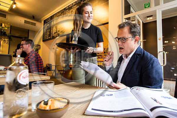 BRUSSELS - BELGIUM - 21 August 2017 -- British EU-Correspondent for the New York Times, James KANTER, wants to change his nationality to the Belgium one because of Brexit. He has to study and learn to speak Flemish for the integration test he has to undergo. Practising his Flemish with waitress Elien in the cafe Markten. -- PHOTO: Juha ROININEN / EUP-IMAGES