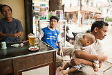 VIETNAM, Hanoi, Bathranag Village, friends smoke and drink at a small street side cafe