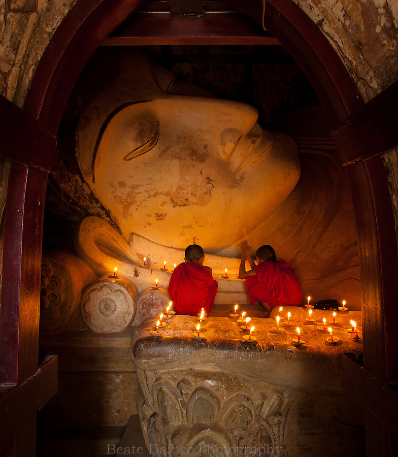 Two monks worshipping at the reclining Buddha in the Shinbinthalyaung temple in Bagan, Myanmar