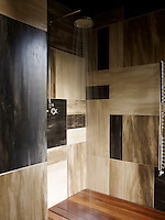 The walls of the walk-in shower are lined with irregular tiles made of horn