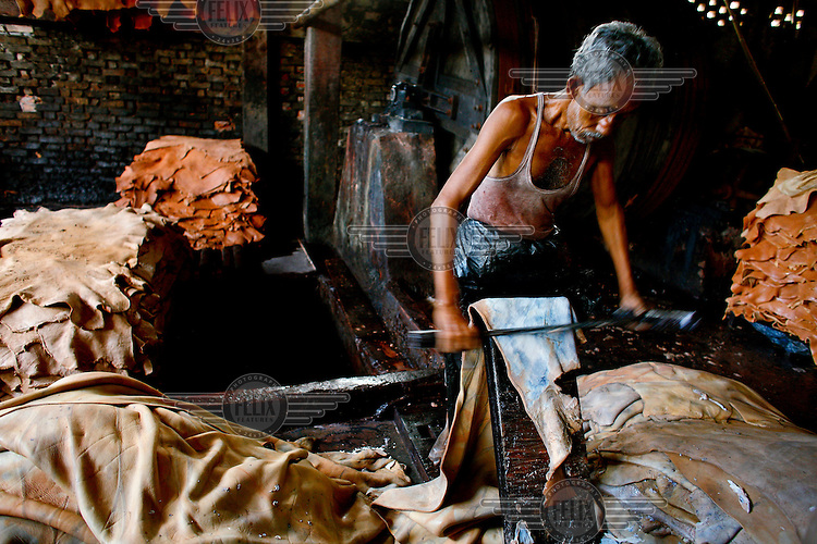 A man scrapes down an animal skin during leather processing in a tannery. It is thought that 90% of tannery workers in Bangladesh suffer from some kind of disease because of chemical exposure while thousands of litres of contaminated water are dumped into the country's rivers.