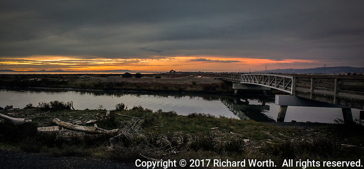 The bridge over San Lorenzo Creek leads to the sunset under an ominous sky along the wetlands on San Francisco Bay's eastern shore.