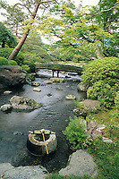 An archetypal Japanese Zen garden featuring a stream, pine trees, a bridge and a stone urn is a paragon of style and quiet elegance.
