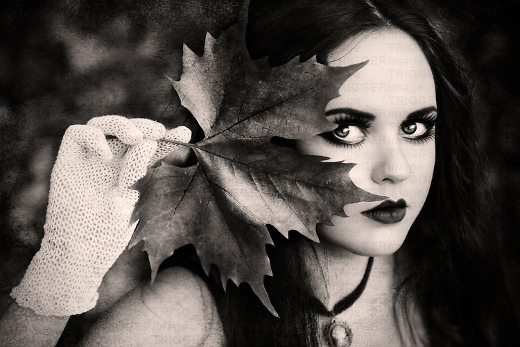 A close-up of a girl with pale skin and long black hair, wearing heavy make-up and holding a large leaf and peeking through it at the camera.