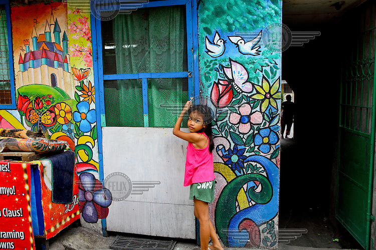 A young girl stands at the door of a house whose walls are brightly decorated with paintings of flowers and birds.