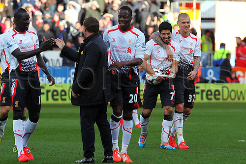 22.03.2014  Cardiff, Wales. Luis Suárez of Liverpool is the hat trick hero as he walks off the pitch with the match ball after scoring three goal during the Premier League game between Cardiff City and Liverpool from Cardiff City Stadium.