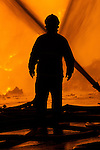 © Joel Goodman . No syndication permitted . 21/08/2013 . Stockport , UK . A firefighter silhouetted against the intense blaze at the J25 Recycling Centre in Bredbury , Stockport this morning (Wednesday 21st August 2013) where a building and bales of recyclable material are alight . The fire , which started late last night (20th August) is being tackled by more than 50 fire crew . The site , which is adjacent to a branch of Morrisons Supermarket and McDonalds , is off Junction 25 of the M60 motorway , exits for which are closed in both directions . Photo credit : Joel Goodman