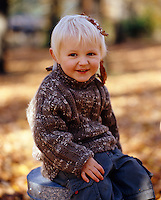 A toddler wearing a warm hand-knitted jumper and with autumn leaves in his blonde hair catches his breath after a leaf fight