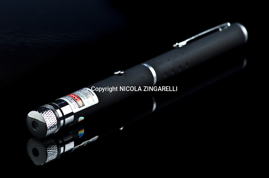 shot of an illegal green laser pen taken in the studio with one light and a black reflecting background