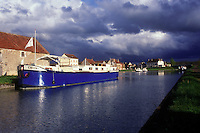 AJ1642, Burgundy, France, canal, barge, Europe, A large blue barge on a the Burgundy Canal with puffy gray clouds in the distance in Burgundy, France.