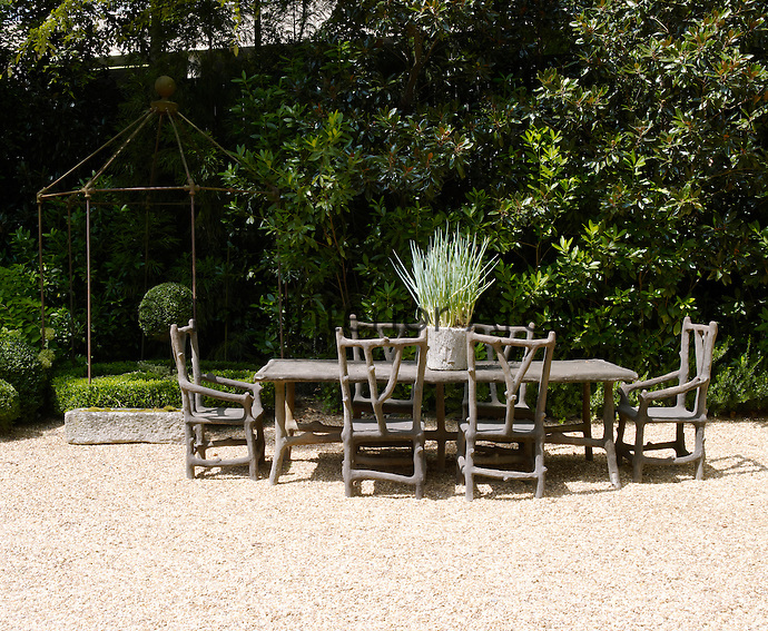 A stone faux-bois dining table from France and an iron gazebo furnish one end of the gravel driveway