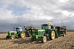 John Deere 4640 (1980) and 4560 (1993) tractors with cotton balers in harvested cotton field; clouds