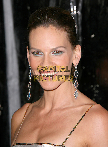 "HILARY SWANK .at the Fox Searchlight Pictures Premiere of ""Conviction"" held at The Academy of Motion Picture Arts and Sciences, Samuel Goldwyn Theatre in Beverly Hills, California, USA, October 5th 2010..portrait headshot smiling hair up ponytail silver dangly earrings green eyeshadow turquoise eyeliner make-up beauty smiling gold .CAP/RKE/DVS.©DVS/RockinExposures/Capital Pictures."