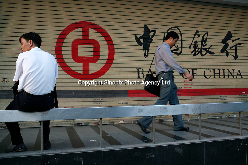 Pedestrians walk past a Bank of China branch in Shenzhen, China. .
