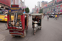 Daytime landscape view of motorized tricycle taxis on the street near the Qiao Jia Men in the Èrqī Qū of Zhengzhou in Henan province.  © LAN