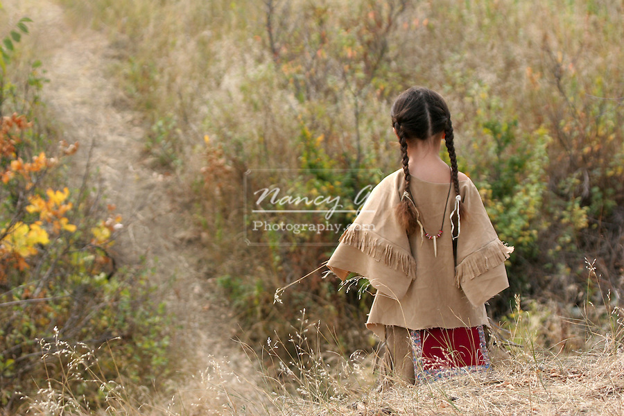 A young Native American Indian boy in braids walking down a path holding a piece of grass