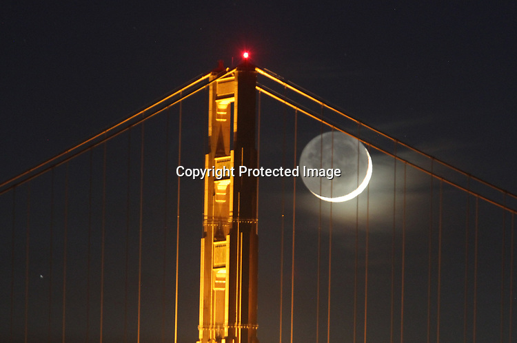 The crescent moon setting behind Golden Gate Bridge as seen from Marina Greens, San Francisco, CA.