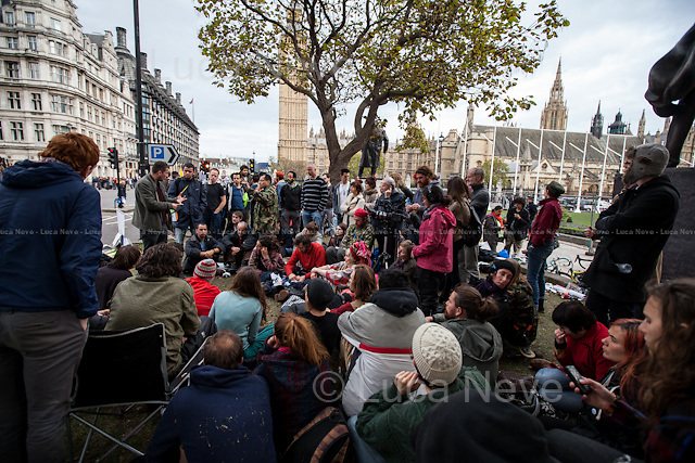 Debating about Kurdish Resistance, Syria, Iraq, Turkey, ISIS (IS or ISIL) and Western Intervention. <br /> <br /> Day X - 26.10.2014 - Farewell To Parliament Square...<br /> <br /> London 17-26.10.2014. A day at the Parliament Square Occupy Democracy Camp in London. Protesters have been camping in Parliament Square since the 17th of October and they will leave on Sunday the 26th. Since the beginning of the direct action protesters have been battling with the MET Police and the Greater London Authority's Heritage Wardens (provided under private contract by AOS Security) over the specific bylaw which applies to a designated area immediately surrounding and including Parliament Square and which bans sleeping equipment. Several people have been arrested, including the Green Party's Baroness Jenny Jones, member of the London Assembly who was later &quot;de-arrested&quot;. In the meantime, numerous celebrities, politicians, experts, activists, and members of the public met for conferences and debates about various topics, from democracy to climate change, to the economic crisis, to corruption, to poetry and many more.<br /> <br /> For more information please click here: http://occupydemocracy.org.uk/ &amp; http://on.fb.me/12tuv79