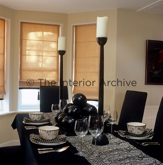 In the black and white dining room a sense of drama is created with the placement of two oversized candlesticks and a pile of black ceramic spheres in the centre of the table