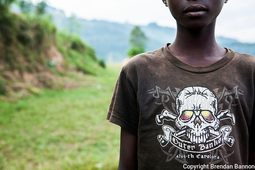 A young boy  wearing a second hand t-shirt at  a rural cattle auction.  Some cattle are sold on the road before they reach the auction site in Kivuruga, Rwanda. Photo by  Brendan Bannon. March 5, 2014