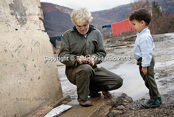 Man works to extract copper wiring from a vaccum cleaner motor while his son watches in the Cesmin Lug IDP camp in northern Mitrovica.