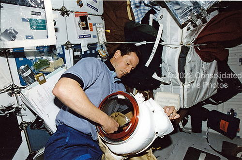 On Discovery's mid deck, astronaut Gregory J. Harbaugh, one half of a space walk team on mission STS-82 to service the Hubble Space Telescope (HST), prepares his extravehicular mobility unit (EMU) space suit for an impending space walk, A total of five days of extravehicular activity (EVA) were used to service the orbiting<br /> observatory.<br /> Credit: NASA via CNP