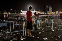 BENICÀSSIM, SPAIN - A festival goer looks on as garbage trucks hoover up thousands of plastic cups and bottles discarded by the main stage of the festival site. ..Described by some as a Mediterranean Glastonbury, the Festival Internacional de Benicàssim (FIB) is the largest music festival outside the UK to target British visitors. In 2010, seven of the eight main headline slots were filled by English bands...A small coastal town of 13,000 inhabitants, Benicàssim hosted some 200,000 visitors in 2009, with 40% of those believed to be coming from the UK. In 2010, attendances fell to 127,000 visitors but the percentage of UK visitors is believed to have risen.