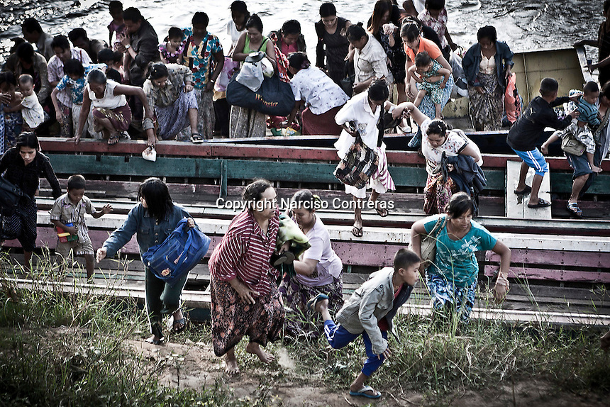 Burmese refugees fleeing into Thailand from clashes between rebel army DKBA and military dictatorship SPDS troops at the bordertown of Myawaddy in Karen state, Burma. Fighting hold last 7th-10th november 2010 sent more than 30,000 refugees into bordertown of Mae Sot. The DKBA Brigade 5 has ordered residents of Myawaddy to evacuate the town. Refugees fled hardly with a few possessions, barefoot, carrying babies and elderly. Group by group jump into the boats while gun shoots and blast rockets sound behind them.