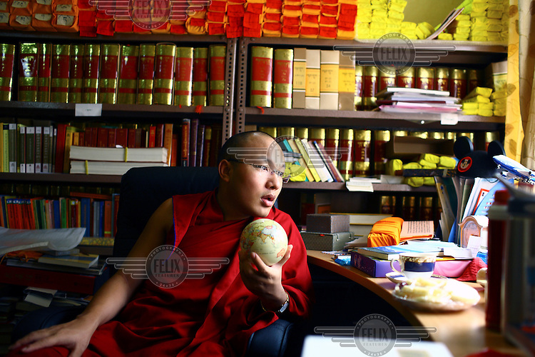 The Seventeenth Karmapa, Ogyen Drodul Trinley Dorje, sits in his library surrounded by Buddist texts and holding a small globe in his hand. In 1992 a 7-year-old Tibetan nomad, Apo Gaga, was recognised as the Seventeenth Karmapa and went to live in Tolung Tsurphu Monastery, the historic seat of the Karmapas. He escaped Tibet for India at the turn of the millennium in order to continue without interference the primary role of the Karmapa, preserving and propagating the Buddhist teachings of Tibet.