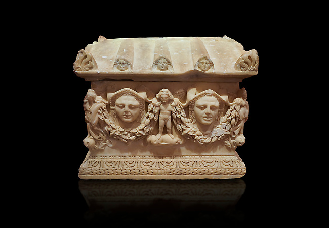Roman relief sculpted Ostothec cremation sarcophagus, 2nd century AD, Perge. An ostothec is used to preserve the ashes and bones of the dead bodies after their cremation, takes its form from a small sarcophagus. This ostothec is a miniature example of the garland sarcophagus. Antalya Archaeology Museum, Turkey.  Against a black background.