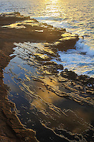 Sunrise at the Lanai Lookout with golden light reflecting off water on a rock shelf, East O'ahu.