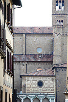 Firenze: A partial view of the ancient church of Santa Maria Novella from faraway. There is the bell tower on the right top, whereas one can see, on the bottom, some of the small arcs with their characteristic alternance of white and blue marble. The photo is taken from a narrow street nearby, typical of the historical center of the town.<br />