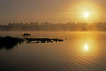 Sunrise at Lake Cassidy in fog with silhouetted fishermen in small rowboat getting ready to cast their lines, east of Marysville, Washington State USA