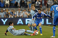 Benny Feilhaber (10) midfield Sporting KC  goes in on a sliding tackle against Andrea Romero (15) forward Montreal Impact..Sporting Kansas City defeated Montreal Impact 2-0 at Sporting Park, Kansas City, Kansas.