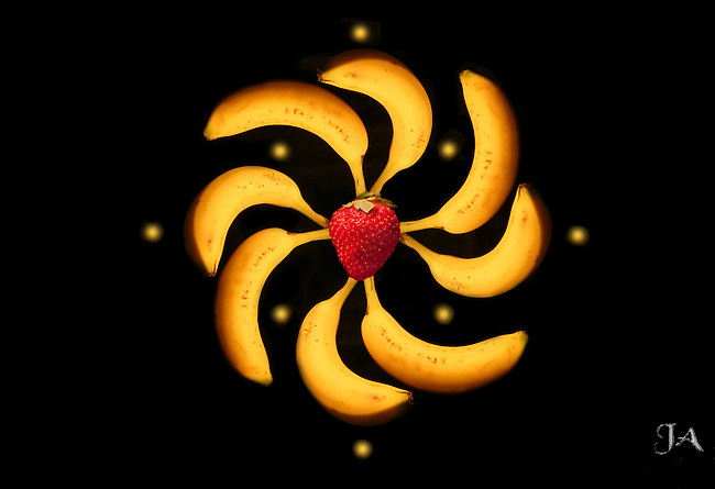 Strawberry banana pinwheel rotating in space surrounded by eight suns.  The bananas are not a manned space station.