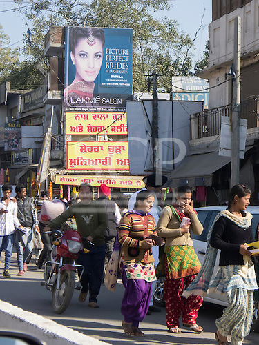 Amritsar, Punjab, India. Street scene; pedestrians passing below an advertisement for 'Picture Perfect Brides' in English with a red and yellow sign in Punjabi below.