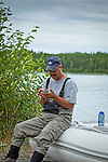 A Alaskan Native man using a smart phone on the boat at Kenai River shore,  Kenai Wildlife Refuge, Southcentral Alaska, Summer.